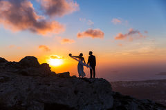 Silhouette of bride and groom on  sea sunset. Silhouette of bride and groom on a high rock on a background of sea sunset Stock Image
