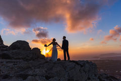 Silhouette of bride and groom on  sea sunset. Silhouette of bride and groom on a high rock on a background of sea sunset Royalty Free Stock Photos