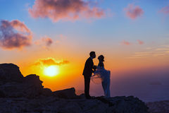 Silhouette of bride and groom on the  sea sunset. Silhouette of bride and groom on a high rock on a background of sea sunset Stock Photo