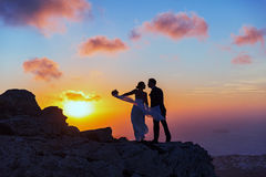 Silhouette of bride and groom on the  sea sunset. Silhouette of bride and groom on a high rock on a background of sea sunset Royalty Free Stock Photo