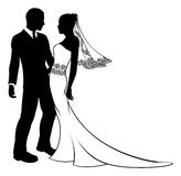 Silhouette of bride and groom wedding couple. Bride and groom embracing at their wedding,  having first dance or about to kiss, with beautiful bridal dress with Stock Images