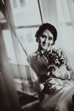 Silhouette of the bride weared in dress and veil with a bouquet Stock Images