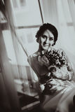 Silhouette of the bride weared in dress and veil with a bouquet Stock Image