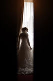Silhouette of a bride at the window Royalty Free Stock Images