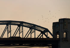 Silhouette of bridge with birds flying over Royalty Free Stock Photography