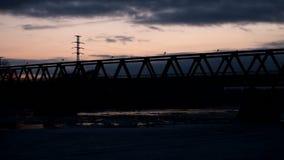 Silhouette bridge in Siberia. Silhouette of a bridge at sunset, far from the Russian hinterland, ice drift under the bridge stock video
