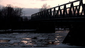 Silhouette bridge in Siberia. Silhouette of a bridge at sunset, far from the Russian hinterland, ice drift under the bridge stock video footage
