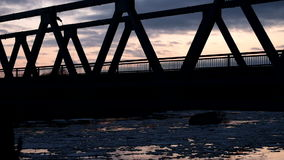 Silhouette bridge in Siberia. Silhouette of a bridge at sunset, far from the Russian hinterland, ice drift under the bridge stock footage