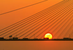 Silhouette of a bridge under setting sun royalty free stock photography
