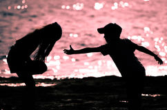 Silhouette of a brother hand helping his sister. Royalty Free Stock Images