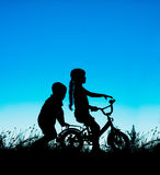 Silhouette of a brother and sister, cycling at sunset Royalty Free Stock Photography