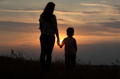Silhouette of a brother and sister at field Royalty Free Stock Images