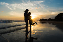 Silhouette of brothers hugging on the beach.  stock image