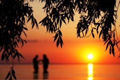 Silhouette brouillée de jeunes couples dans l'amour, se tenant en mer Photographie stock