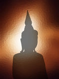 Silhouette Buddha image over brown light sunset backgro Stock Images