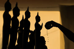 Silhouette of Buddha pouring water to Buddha statue in Songkran Stock Photography