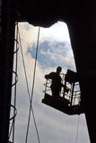 Silhouette of builder working at height Stock Photography