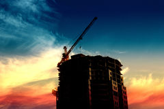 Silhouette of the building and construction cranes. In the background of the sunset sky Stock Images