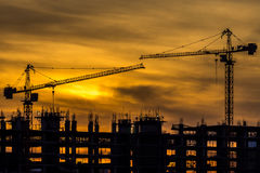 Silhouette of building and crane Stock Photography