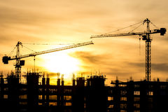 Silhouette of building and crane Stock Photos