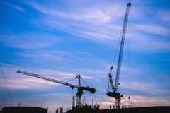 Silhouette building and cranes sunset scene. Royalty Free Stock Images