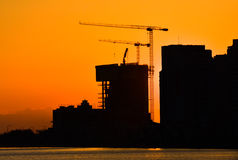 Silhouette of building under construction and the construction crane or power crane sunset time. Stock Photo