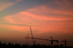 Silhouette of buildings and construction cranes against twilight pastel orange and blue sky. Bangkok, Thailand Stock Photography