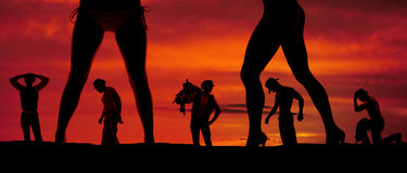 Silhouette of a bunch of cowboys and two womens legs Stock Image