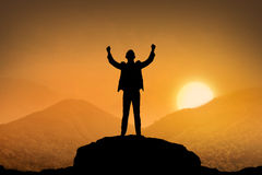 Silhouette business man standing top of the mountain. When sunset come Stock Photo