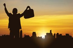 silhouette of business man and successful person celebration holding document bag and standing on top of bouilding with happiness stock images