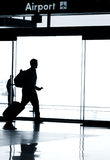 Silhouette of business man walking in airport. Business travel photo concept - Silhouette of business man walking in airport with luggage Royalty Free Stock Photos