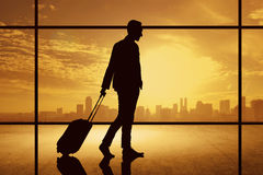 Silhouette of business man walking with suitcase over city background Stock Photos