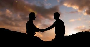 Silhouette business partners shaking hands on mountains during sunset. Digital composite of Silhouette business partners shaking hands on mountains during sunset Stock Image