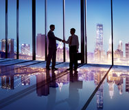 Silhouette of Business People Hand Shaking in the Office Stock Images