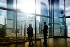Silhouette of Business People Posing by Window. Silhouette of businessmen on windows.  Royalty Free Stock Images