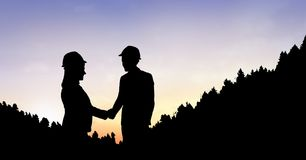 Silhouette business people shaking hands on mountain during sunset Stock Photography