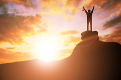 Silhouette business people victory raising hands and holding gold medal with sunset sky on mountain. Motivation and success. Concept royalty free stock photos