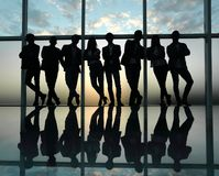 Silhouette of a business team standing next to the office window stock photos