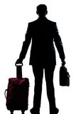 Silhouette business traveler man with suitcase. Rear view one caucasian business traveler man walking with suitcase standing  full length silhouette in studio Stock Photography