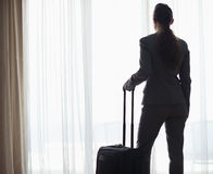 Silhouette of business woman with bag looking into window Stock Images