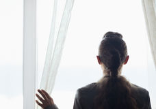 Silhouette of business woman looking into window. Silhouette of modern  business woman looking into window Royalty Free Stock Image