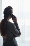 Silhouette of business woman talking cell phone. And looking into window Stock Image