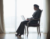 Silhouette of business woman working on laptop Stock Photo