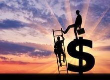 Concept of greed and inequality. Silhouette of a businessman climbs the stairs, and another businessman standing on a dollar symbol pushes this ladder. The stock photography