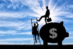 Concept of greed and inequality. Silhouette of a businessman climbs the stairs, and another businessman standing with a piggy bank pushes this ladder. The Stock Image