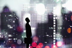 Silhouette of businessman holding a briefcase with a city at night time in the background Royalty Free Stock Images