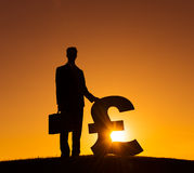 Silhouette of Businessman Holding Currency Sign Royalty Free Stock Images