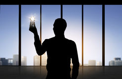Silhouette of businessman holding light bulb Royalty Free Stock Photo