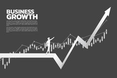 Silhouette of businessman point to higher of graph stock image