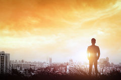 Silhouette of businessman to city way light the sunset. Stock Image